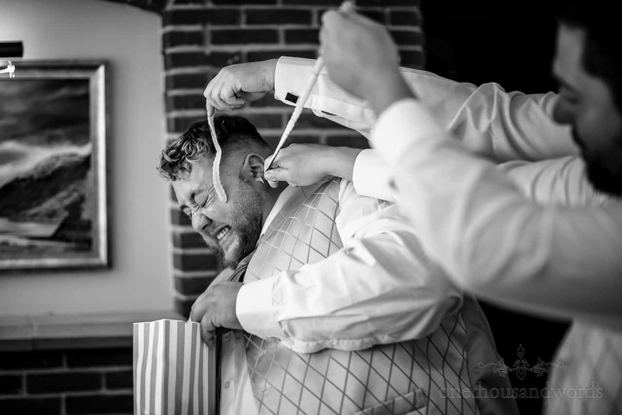Black and white documentary wedding photo of best man being attacked by jelly snakes