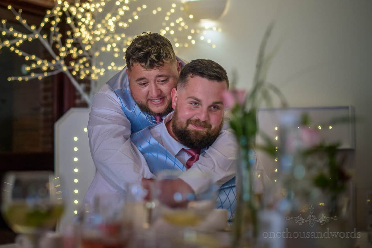 Documentary wedding photo of best men hugging wearing blue patterned waistcoats