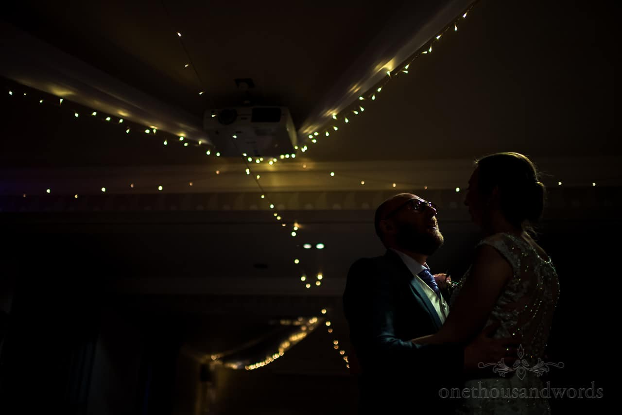 Documentary wedding photograph of bride and groom's first dance under fairy lights