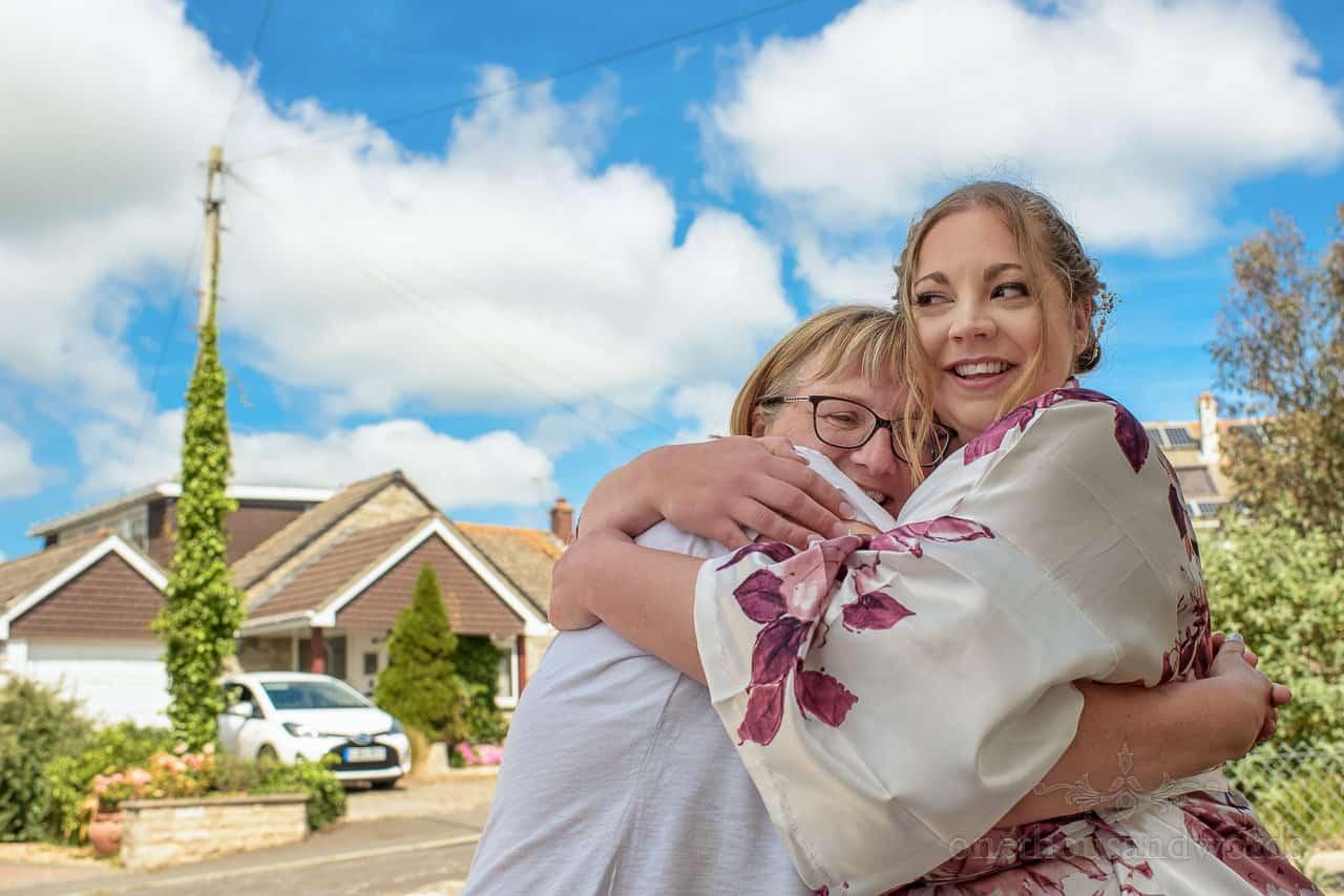 Documentary wedding photo of bride hugging family member on wedding morning outside family home