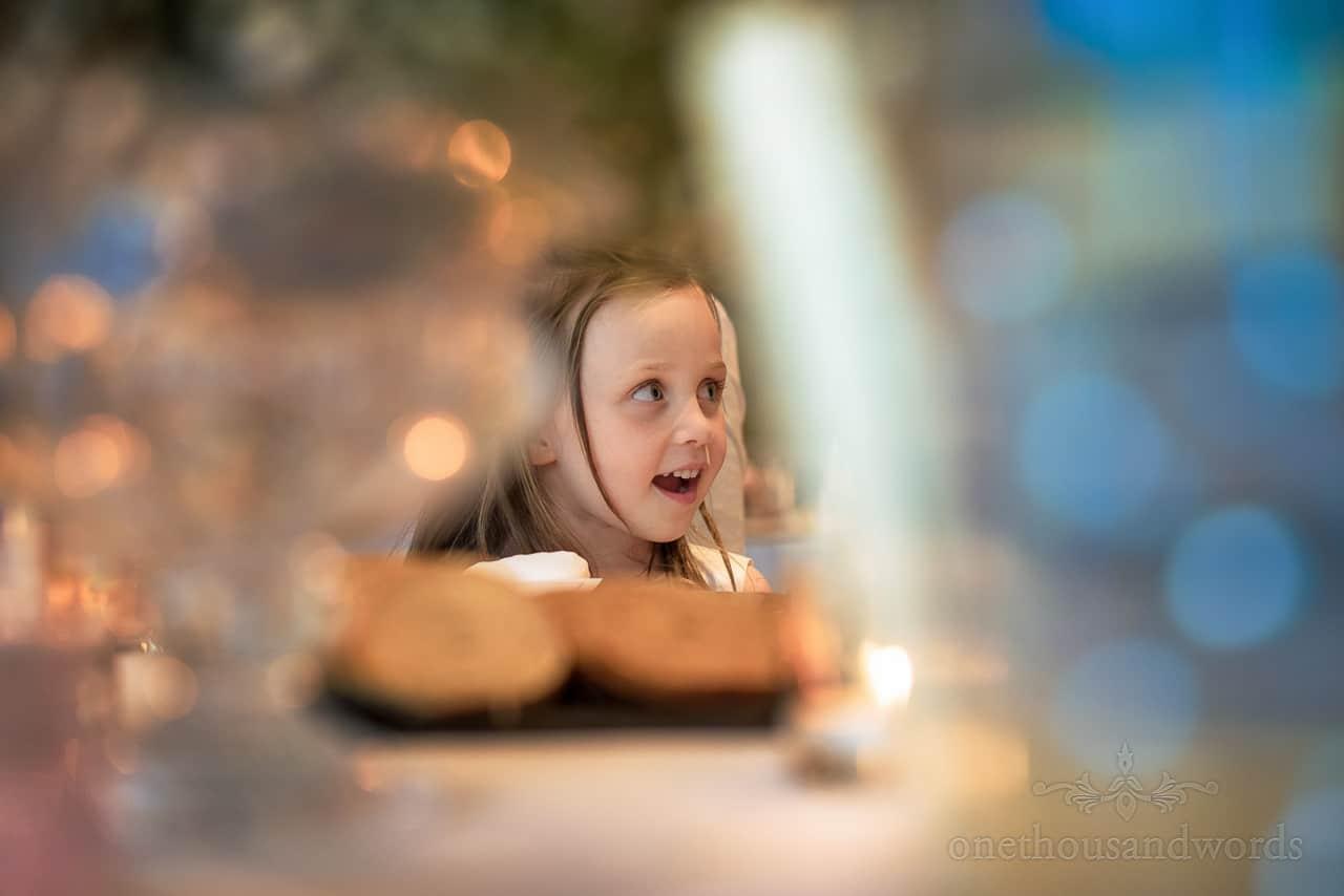 Flower girl portrait photograph at wedding breakfast taken through wine glasses