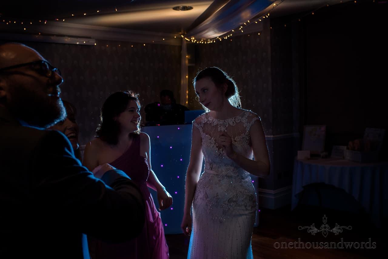 Documentary wedding photo of rim lit bride and bridesmaid dancing at hotel wedding