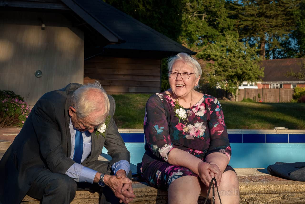 Elderly wedding guests laughing in hotel gardens sat next to swimming pool