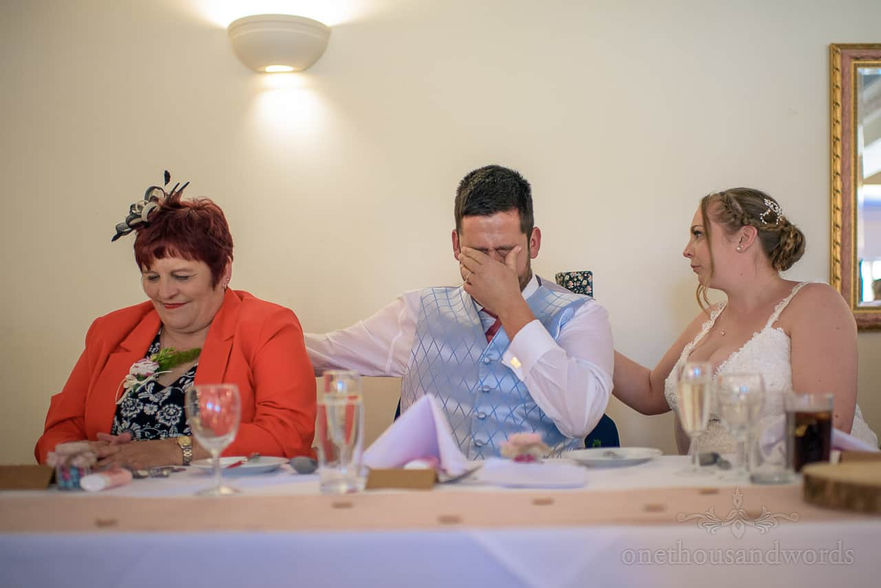 Emotional groom cries during wedding speeches, comforted by bride at top table