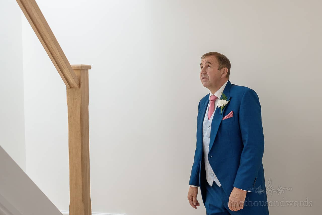 Father of the bride in blue wedding suit looks up stairs to see the bride in her wedding dress