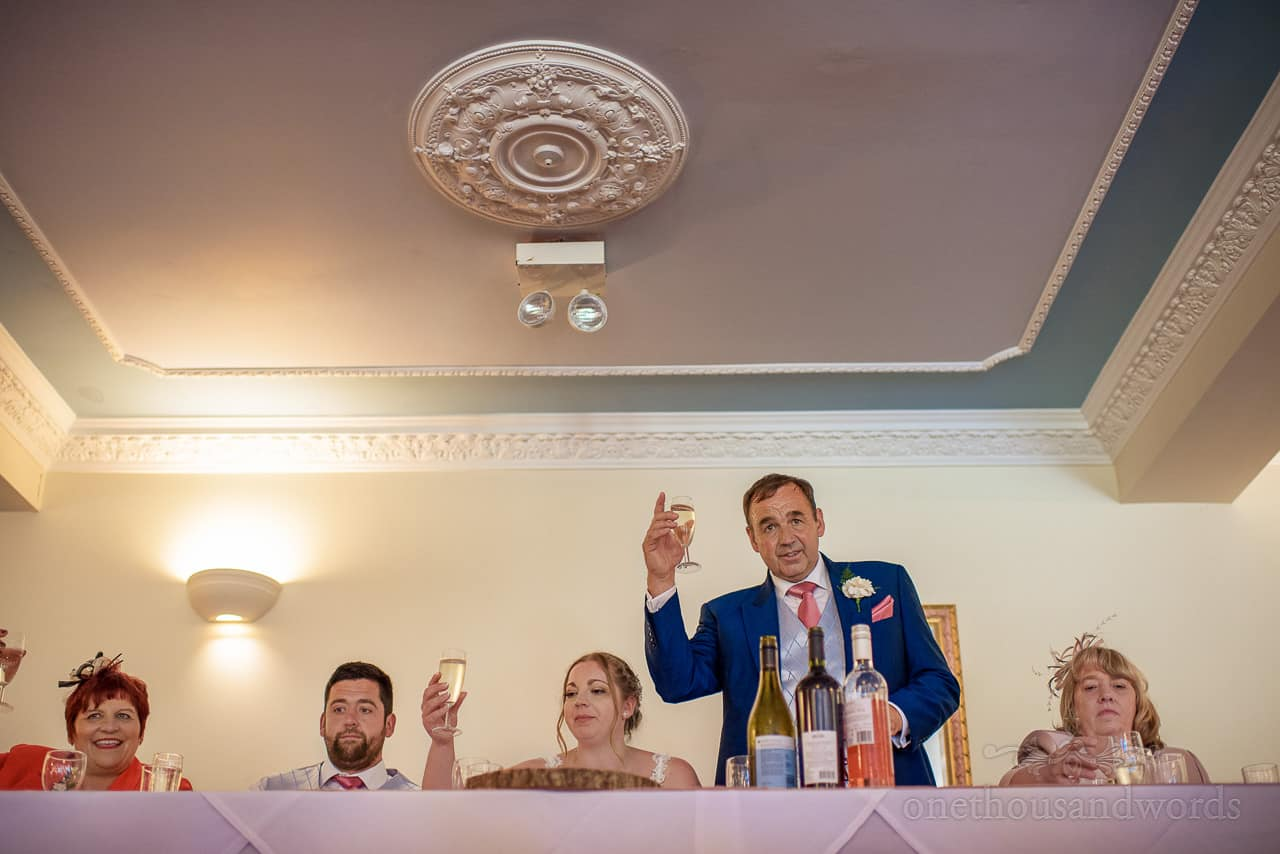 Father of the bride raises a glass for toasts during wedding speech from top table