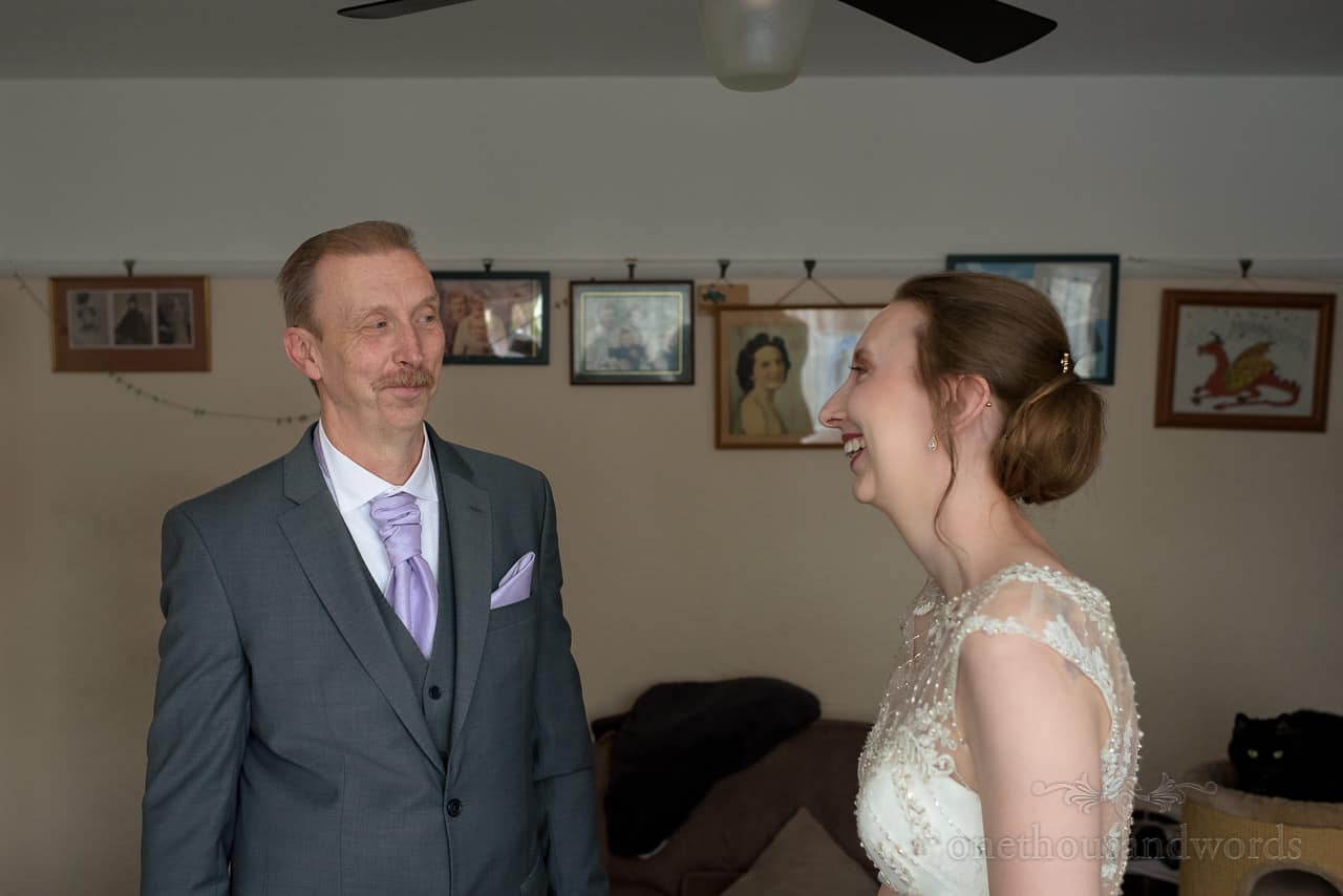 Father of the bride's happy reaction to seeing bride in her wedding dress for the first time at family home on wedding morning