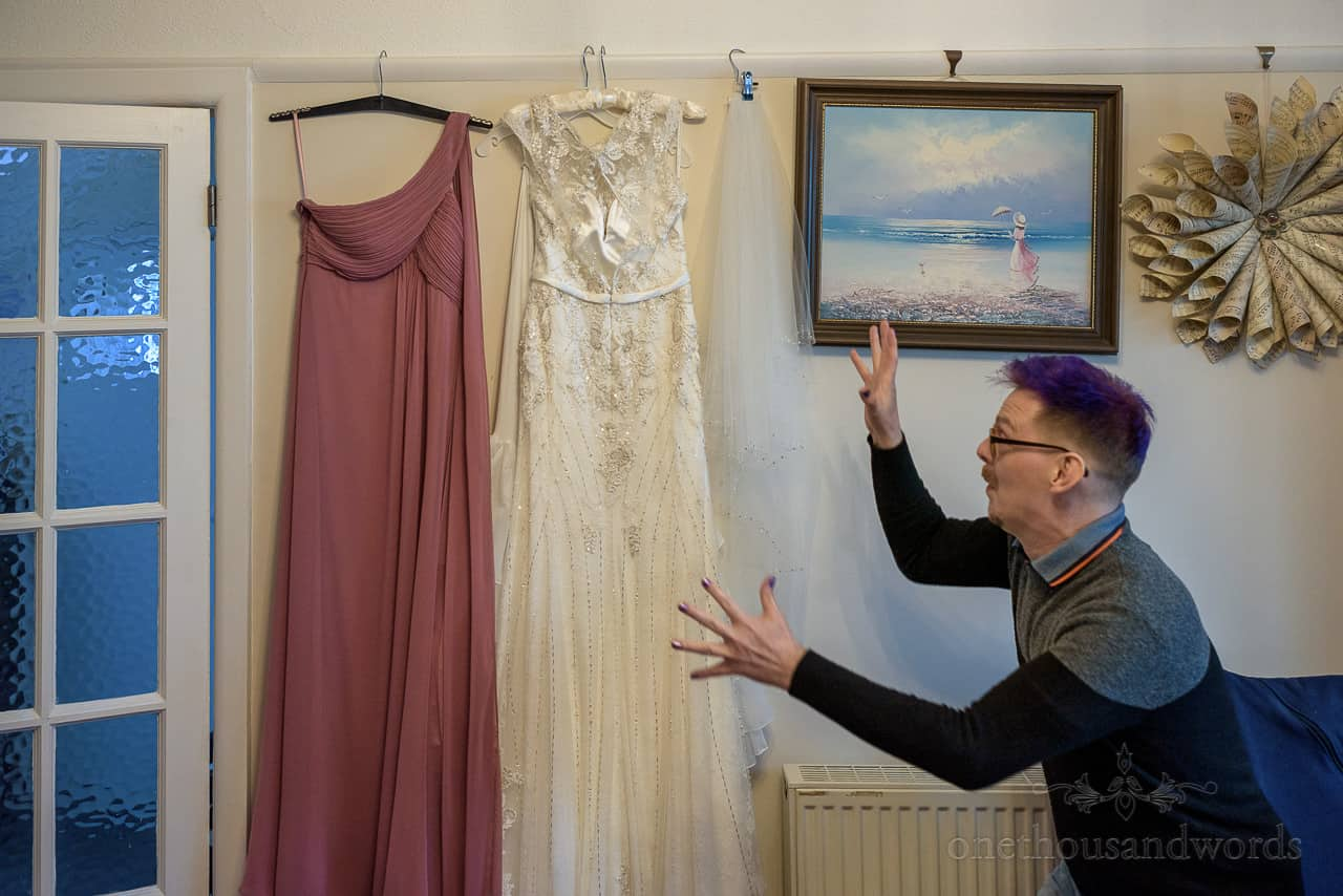 Funny bridesman with purple hair pretends to claw at mauve bridesmaid dress and white wedding dress