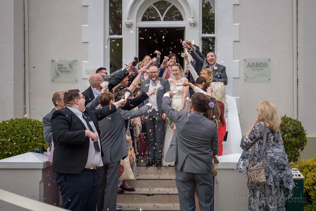 Wedding confetti is thrown over bride and groom exiting The Green House wedding venue in Bournemouth