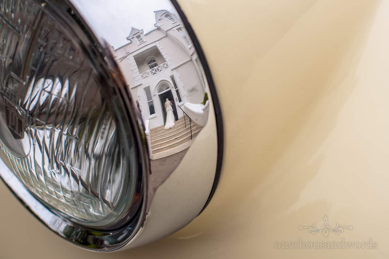 Reflection photo of bride at The Green House Hotel wedding venue in classic wedding car chrome headlight