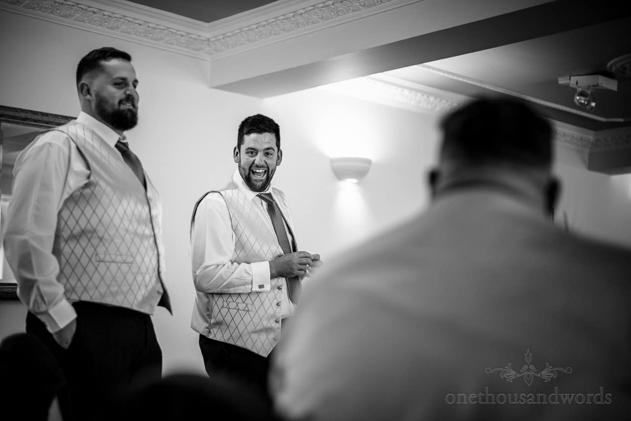 Groom laughing with best men at wedding reception in black and white documentary wedding photograph