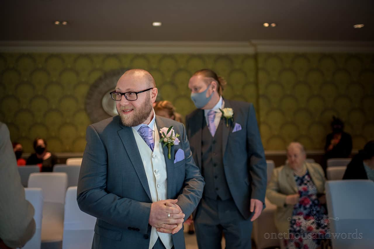Groom in grey and cream wedding suit waits for bride at Green House Hotel wedding ceremony