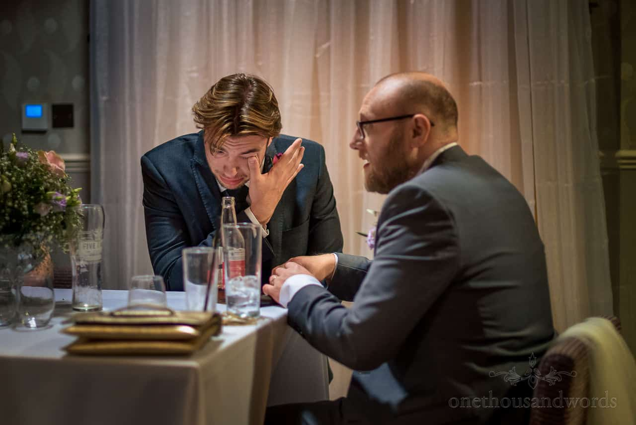 Groomsman cries as he talks to the groom at wedding evening reception