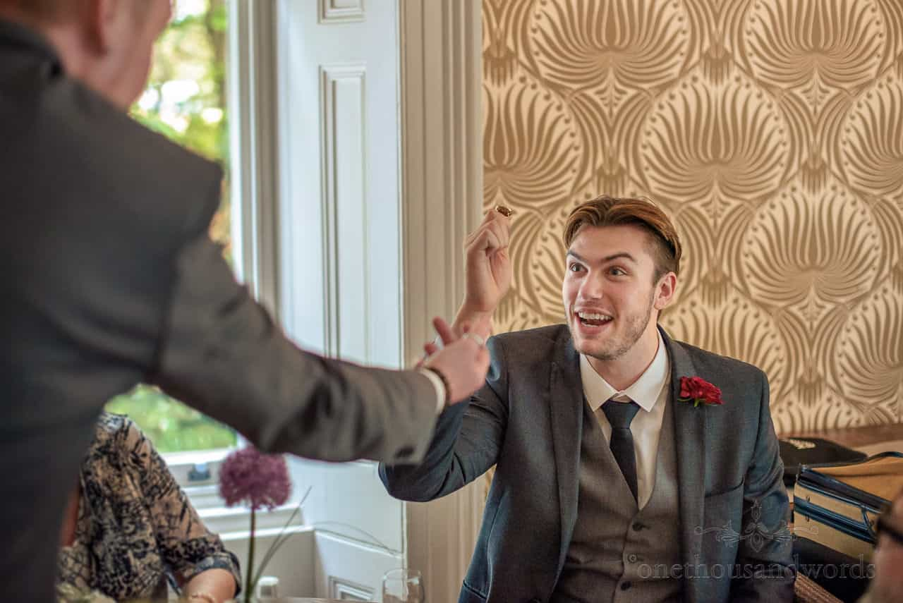 Groomsman in three piece grey suit has animated expression during wedding drinks reception
