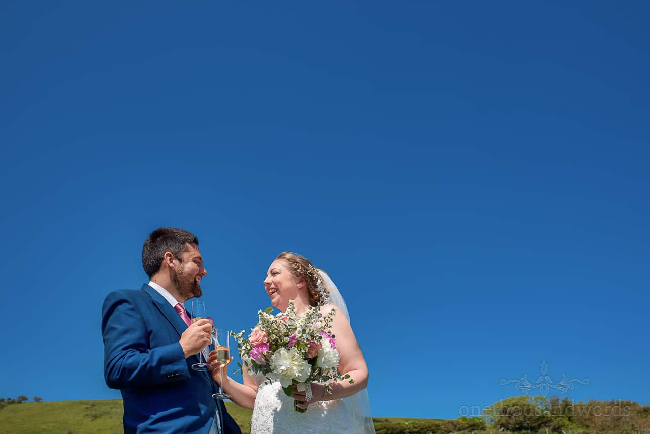 Happy bride and groom couple photograph in Dorset countryside with glasses of champagne and wedding flower bouquet