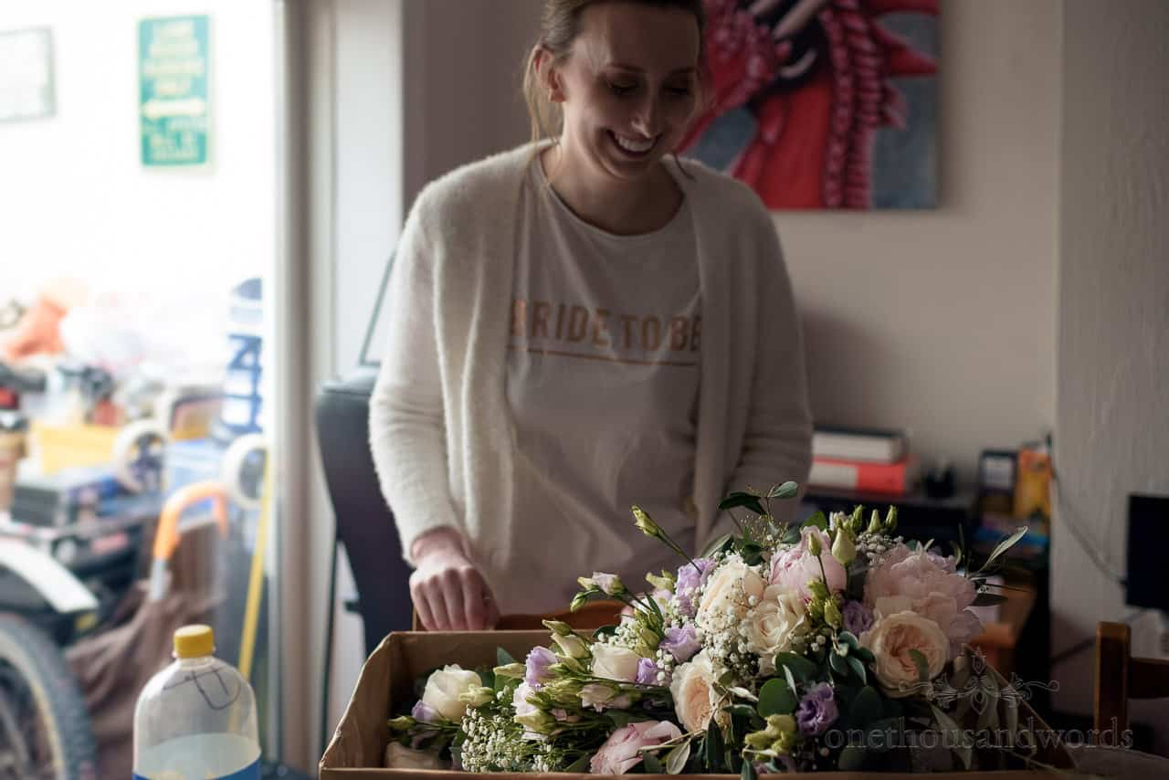 Happy bride to be sees her wedding flower bouquet for first time at home on wedding morning