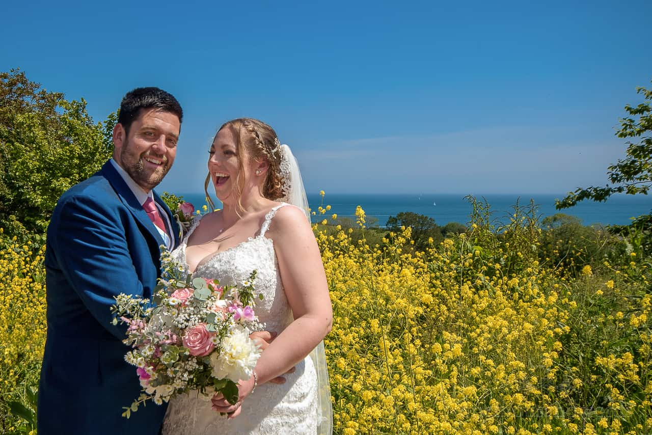 Laughing bride and groom couple photo in Dorset countryside with bright yellow flowers and blue sea and sky