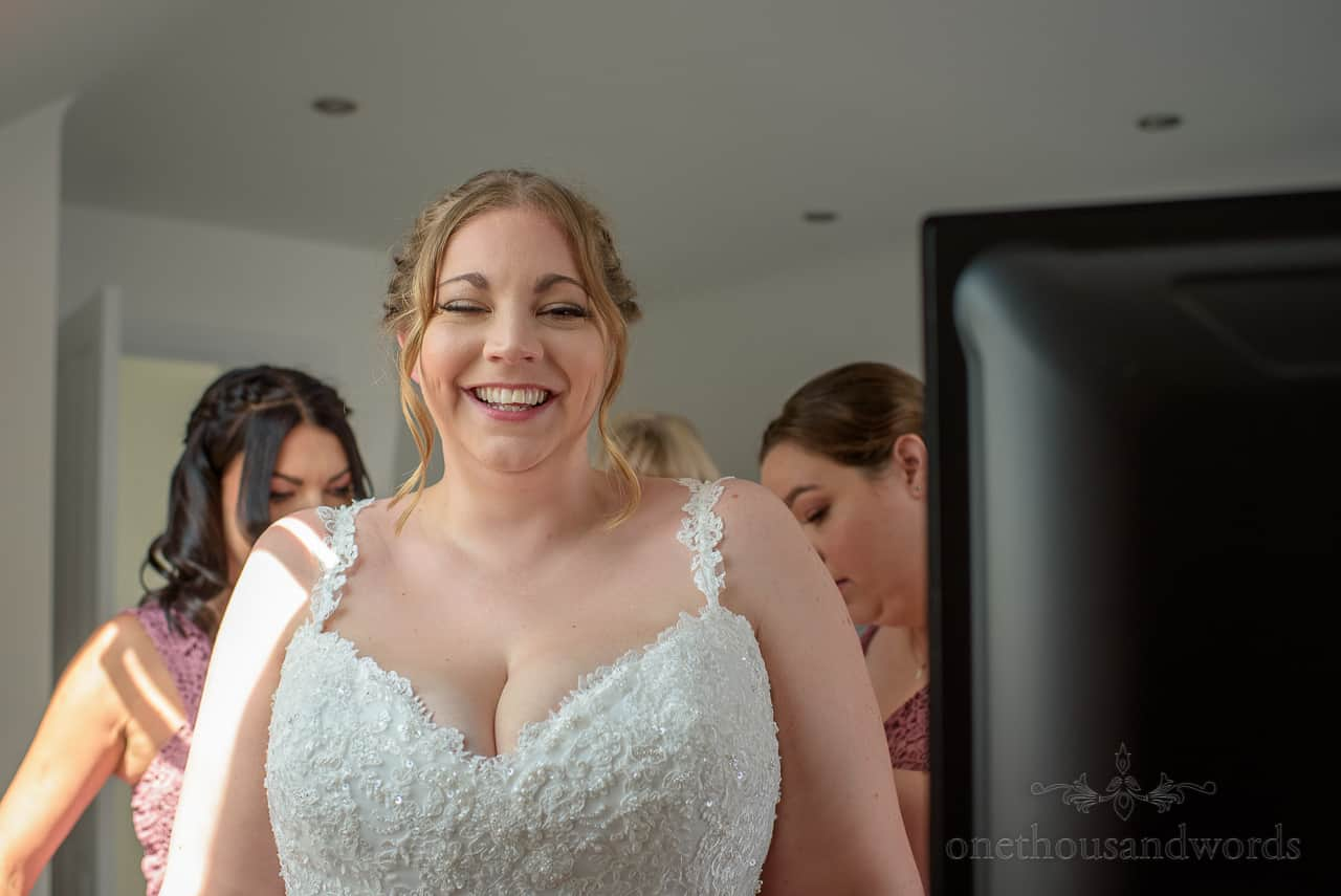 Laughing bride portrait photo taken as she is laced into her white wedding dress by bridesmaids