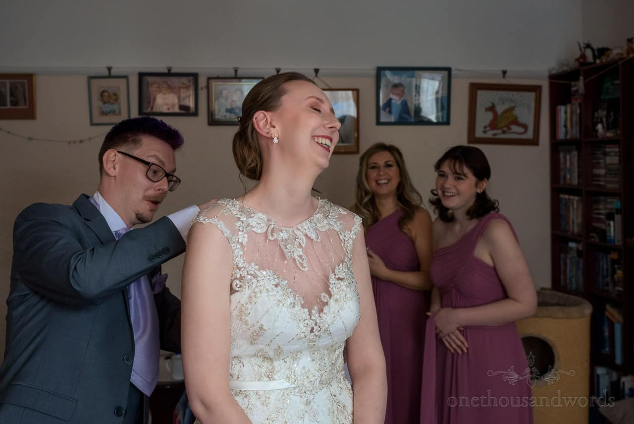 Laughter as bride is helped into her white wedding dress