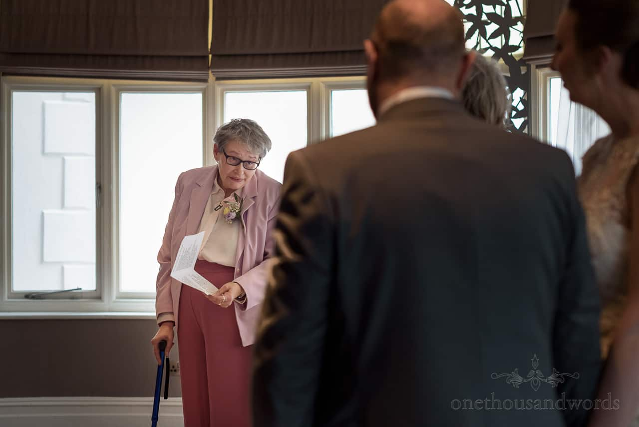 Mother of the bride finishes reading during hotel wedding ceremony