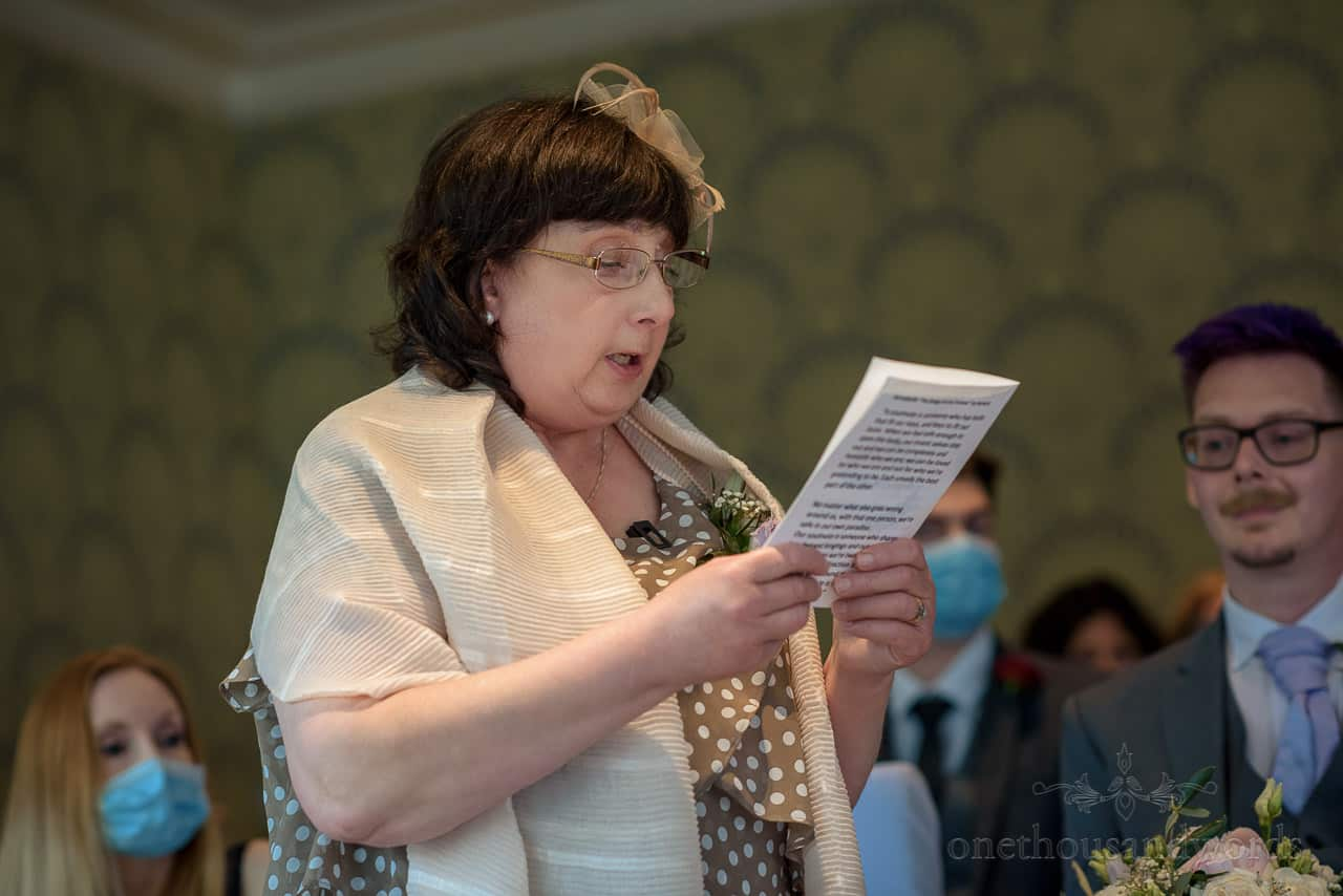 Mother of the groom in polka dot dress and fascinator makes wedding ceremony reading