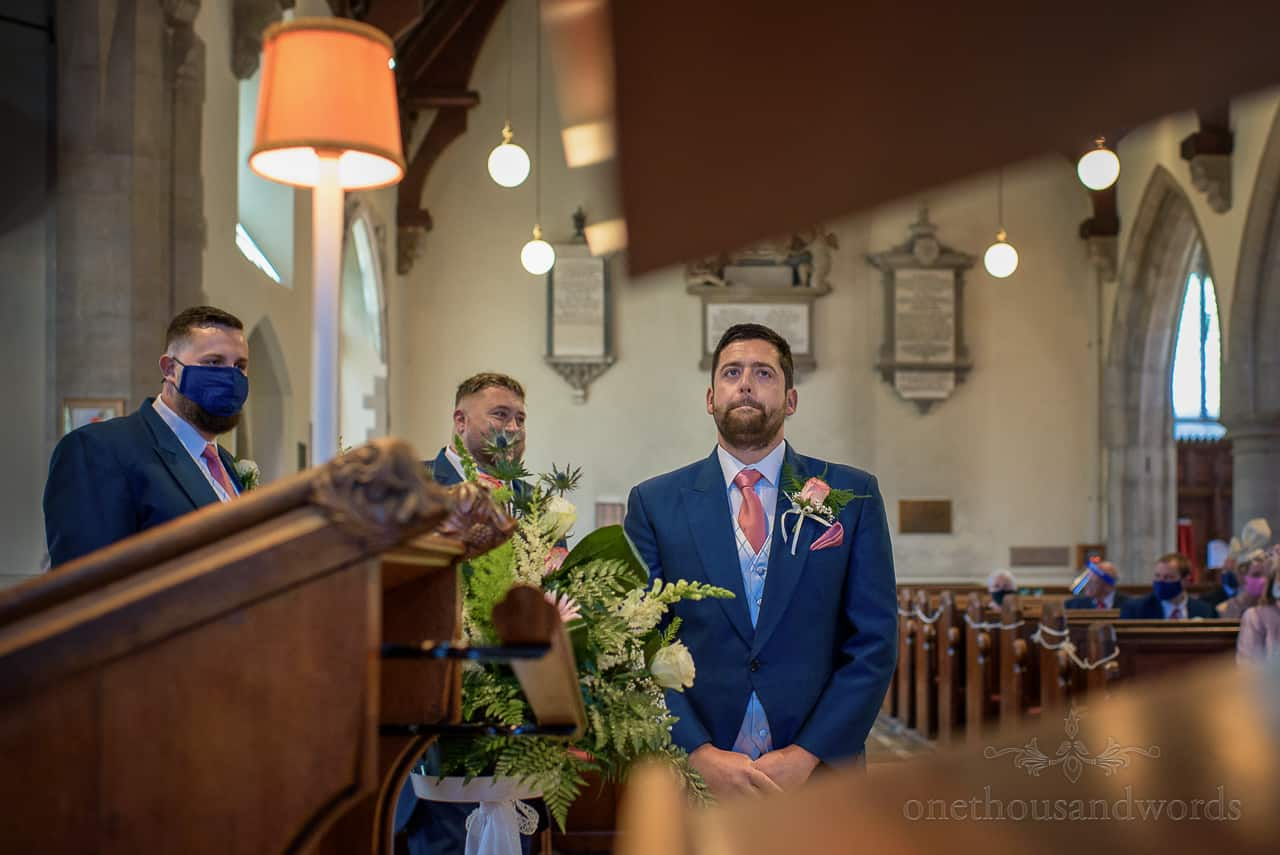 Nervous looking groom in blue suit waiting in church for bride