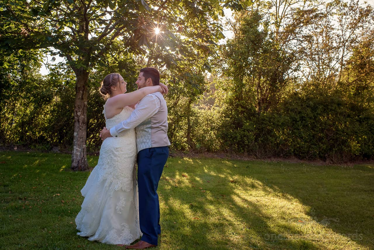 Outdoor first dance by bride and groom in hotel gardens with low sun