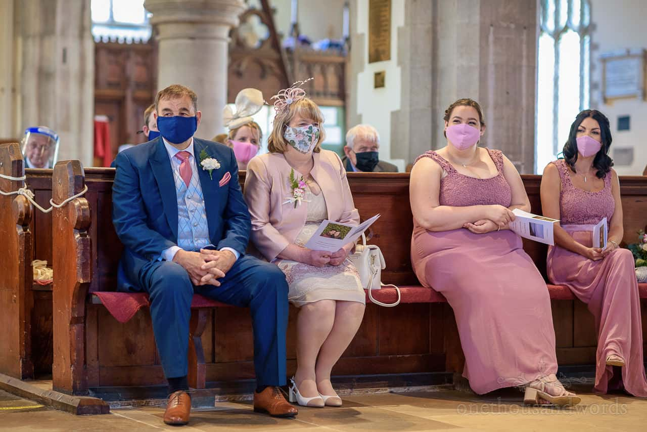 Parents and bridesmaids wearing COVID masks during church wedding ceremony