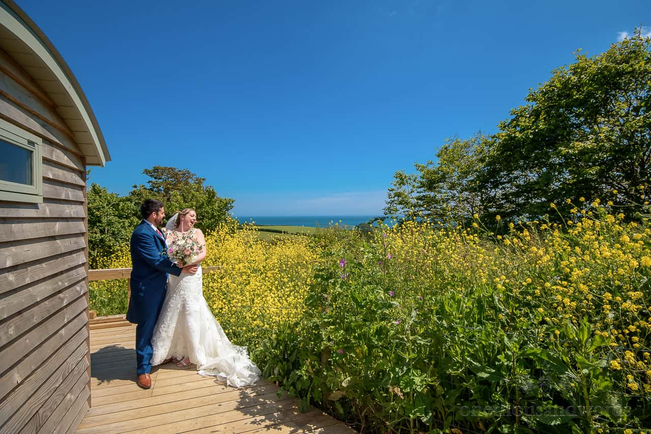 Singing bride during couple photographs in Dorset countryside with shepherds hut, yellow flowers and blue sea
