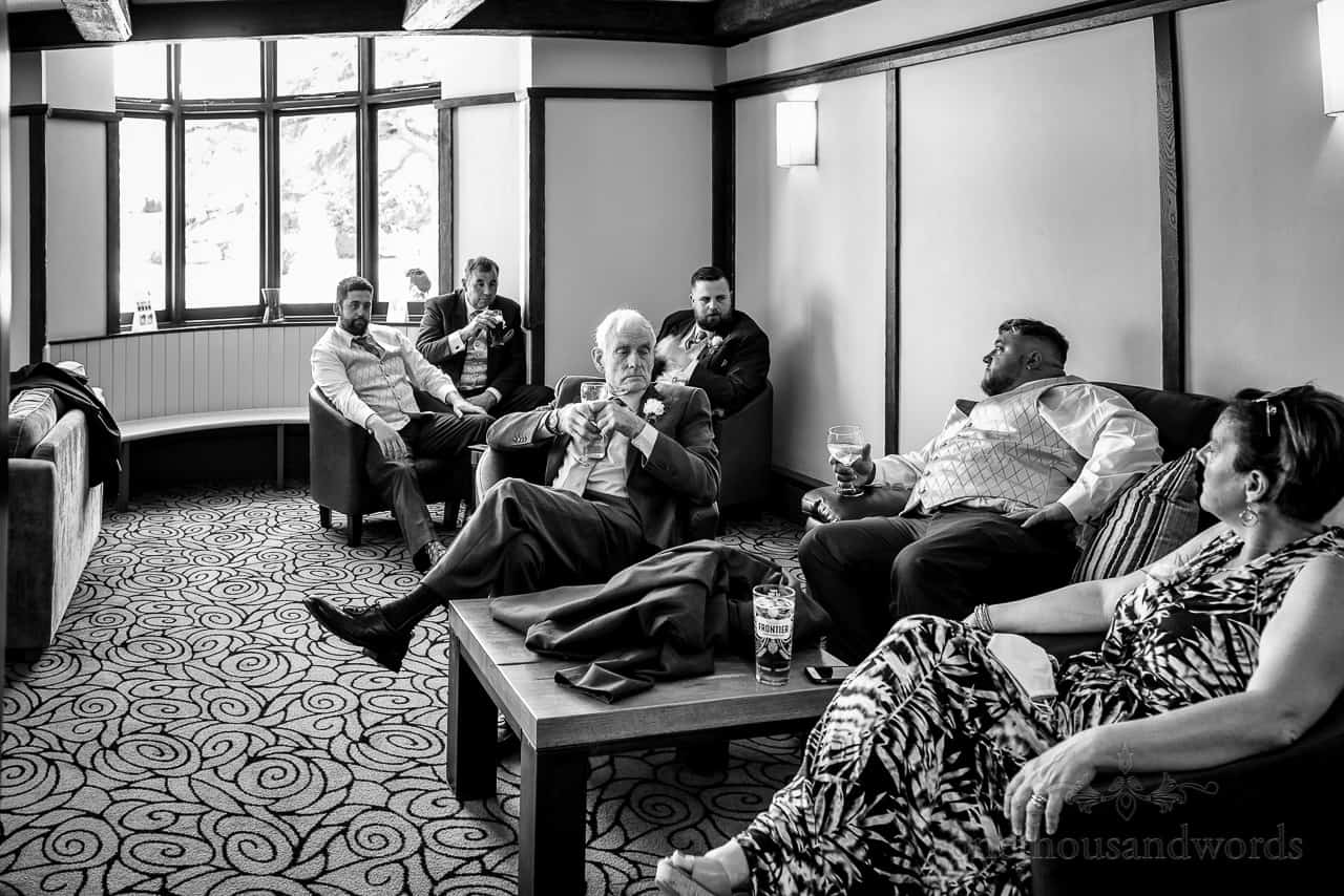 Black and white documentary wedding photograph of guests relaxing in Springfield Hotel bar