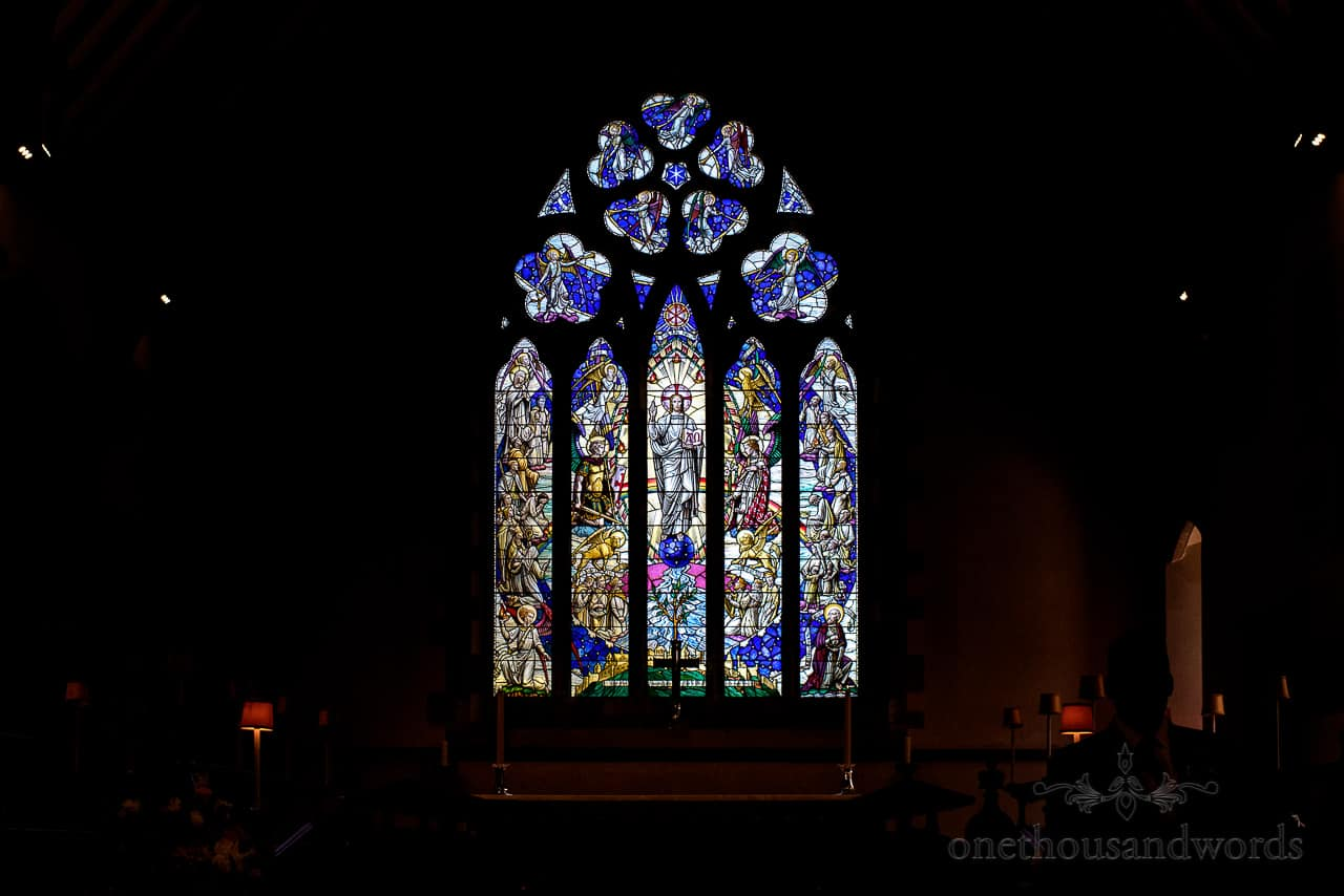 Colourful stained glass window glowing at St Marys Church wedding venue in Swanage, Dorset
