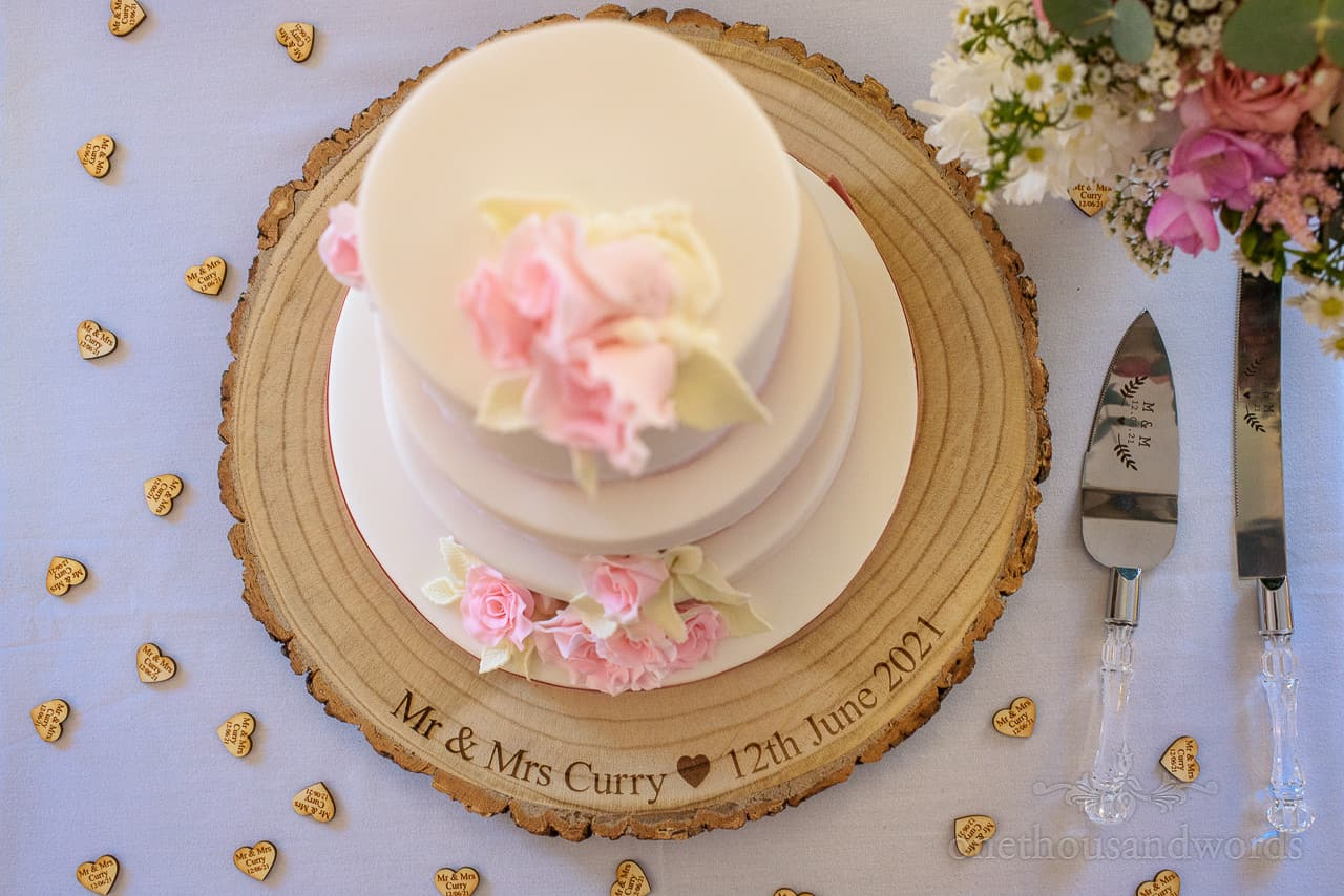 Tiered white wedding cake with custom engraved log slice, wooden love hearts and pink sugar flowers