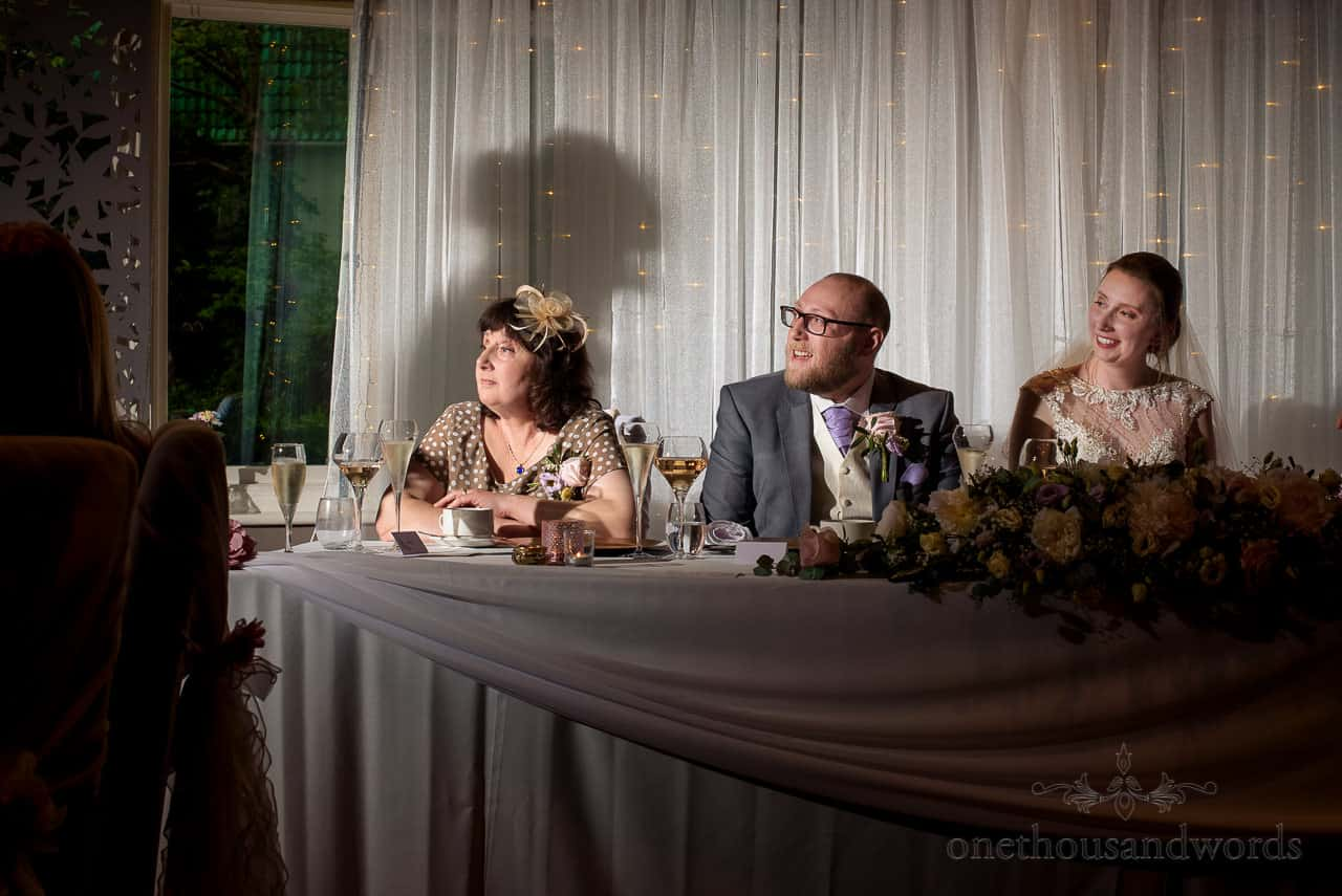 Top table reactions to wedding speeches with wedding speakers shadow projection