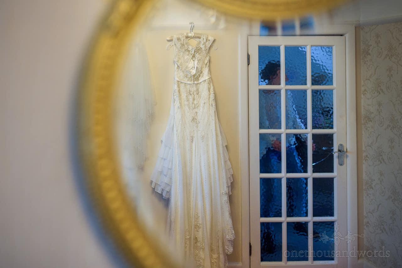 Mirror reflection of hanging wedding dress with bride walking past illuminated door