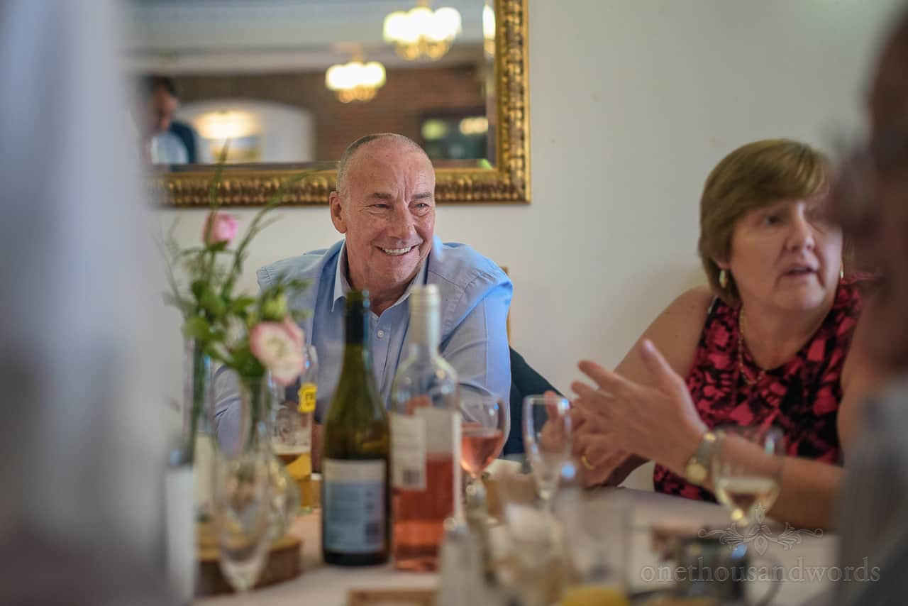 Male wedding guest laughing at wedding breakfast conversation in Springfield hotel wedding venue