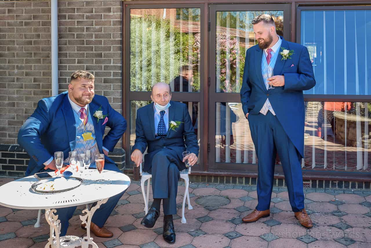 Wedding guests in blue suits laugh at bad COVID facemask placement