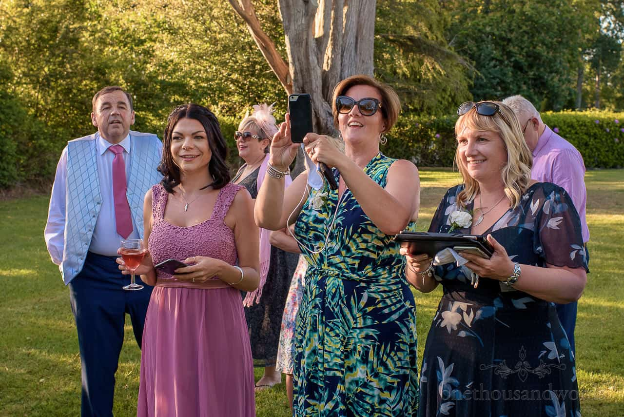 Wedding guests laughing and taking photos of outdoor first dance in gardens