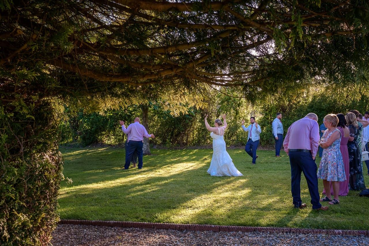 Wedding party dancing outdoors in hotel wedding venue gardens in Dorset