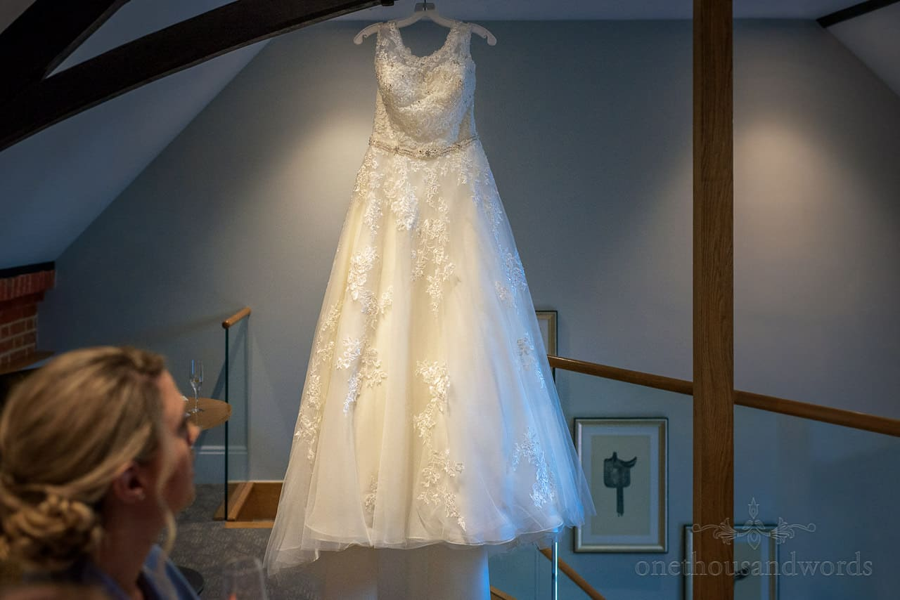 A Line wedding dress hanging in rafters with lace floral detail