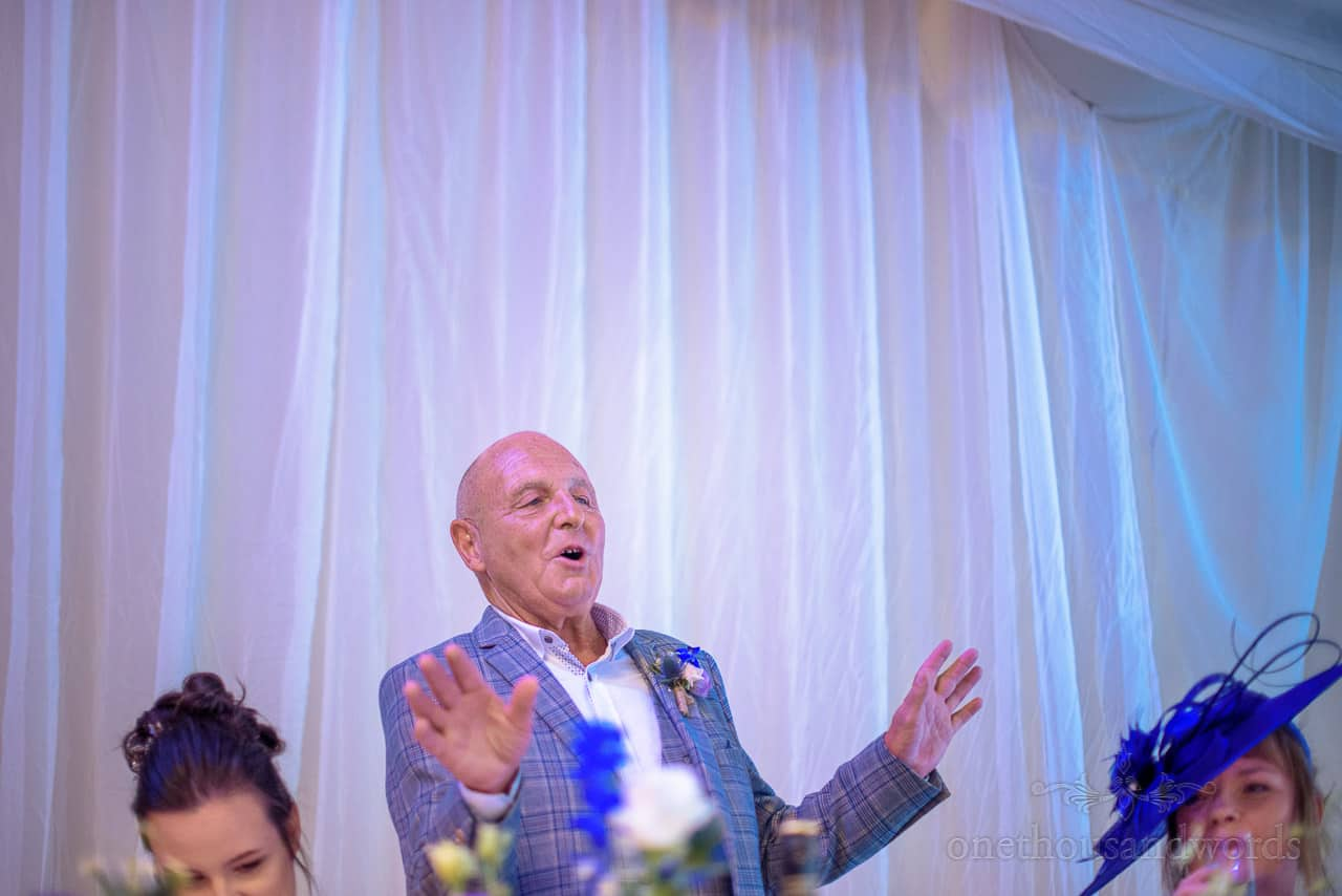 Animated father of the bride speech at top table in wedding marquee
