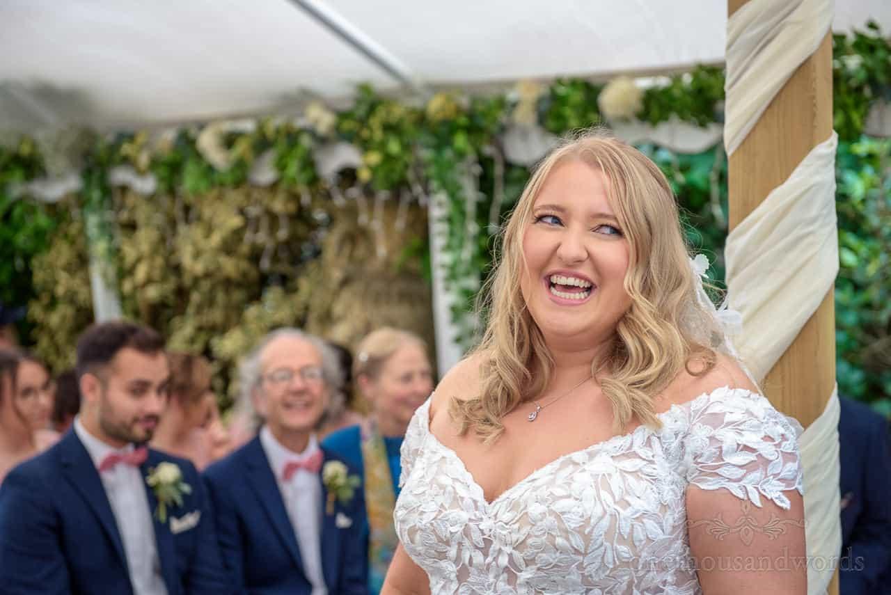 Beautiful blonde bride laughing with registrar at Hethfelton House wedding ceremony