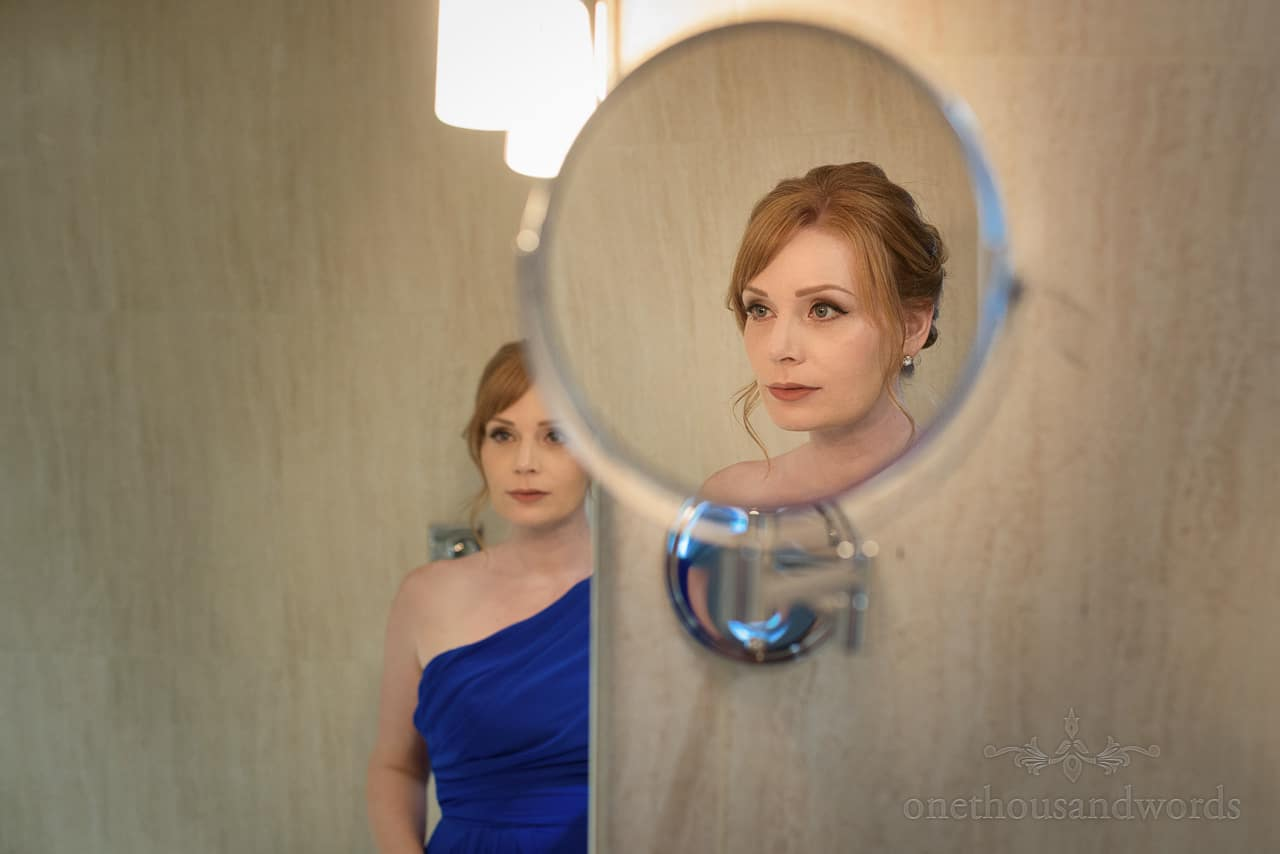 Beautiful ginger haired bridesmaid in blue dress portrait reflection photo in bathroom mirror