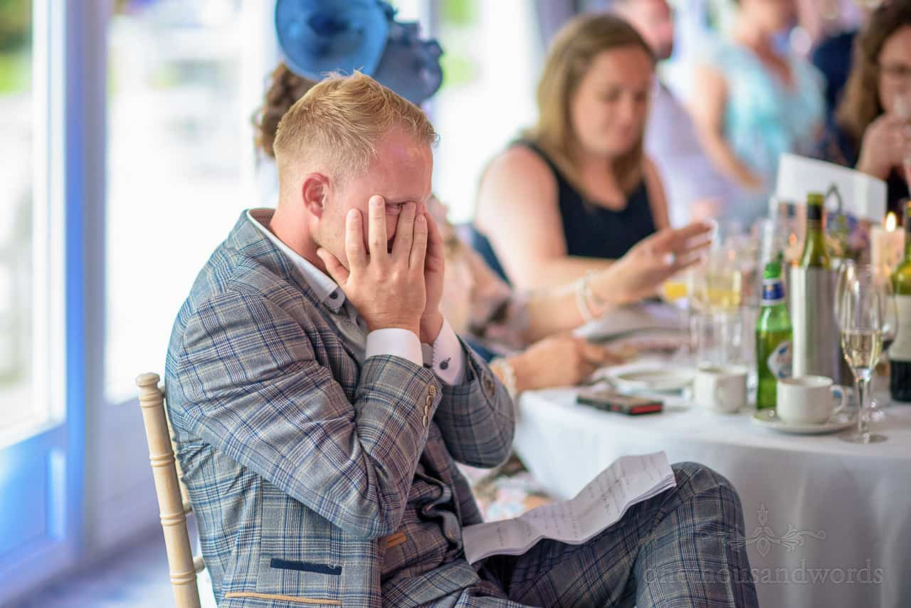 Best man cringing with hands over his face during wedding speeches