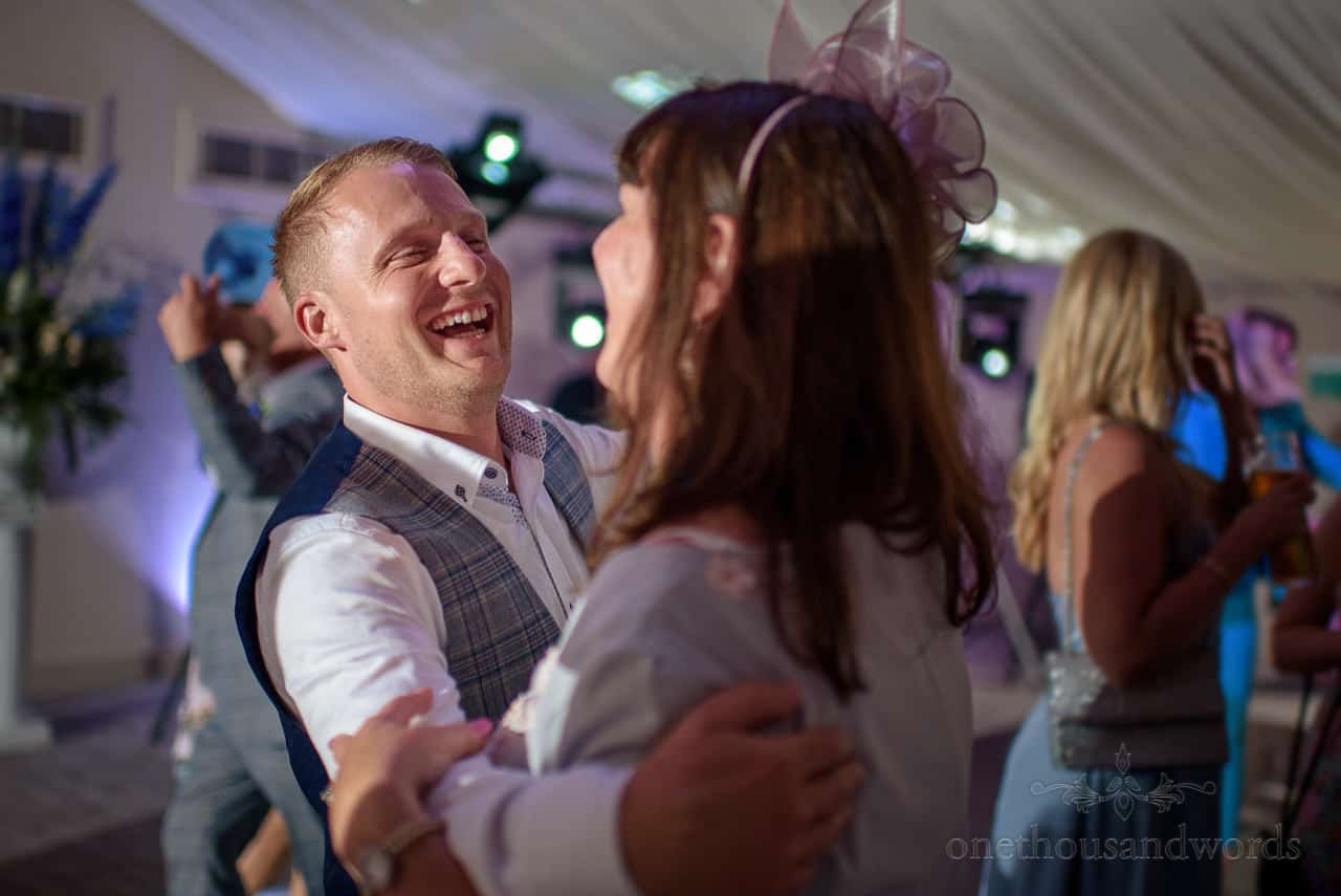 Best man dancing and laughing at marquee wedding evening reception disco