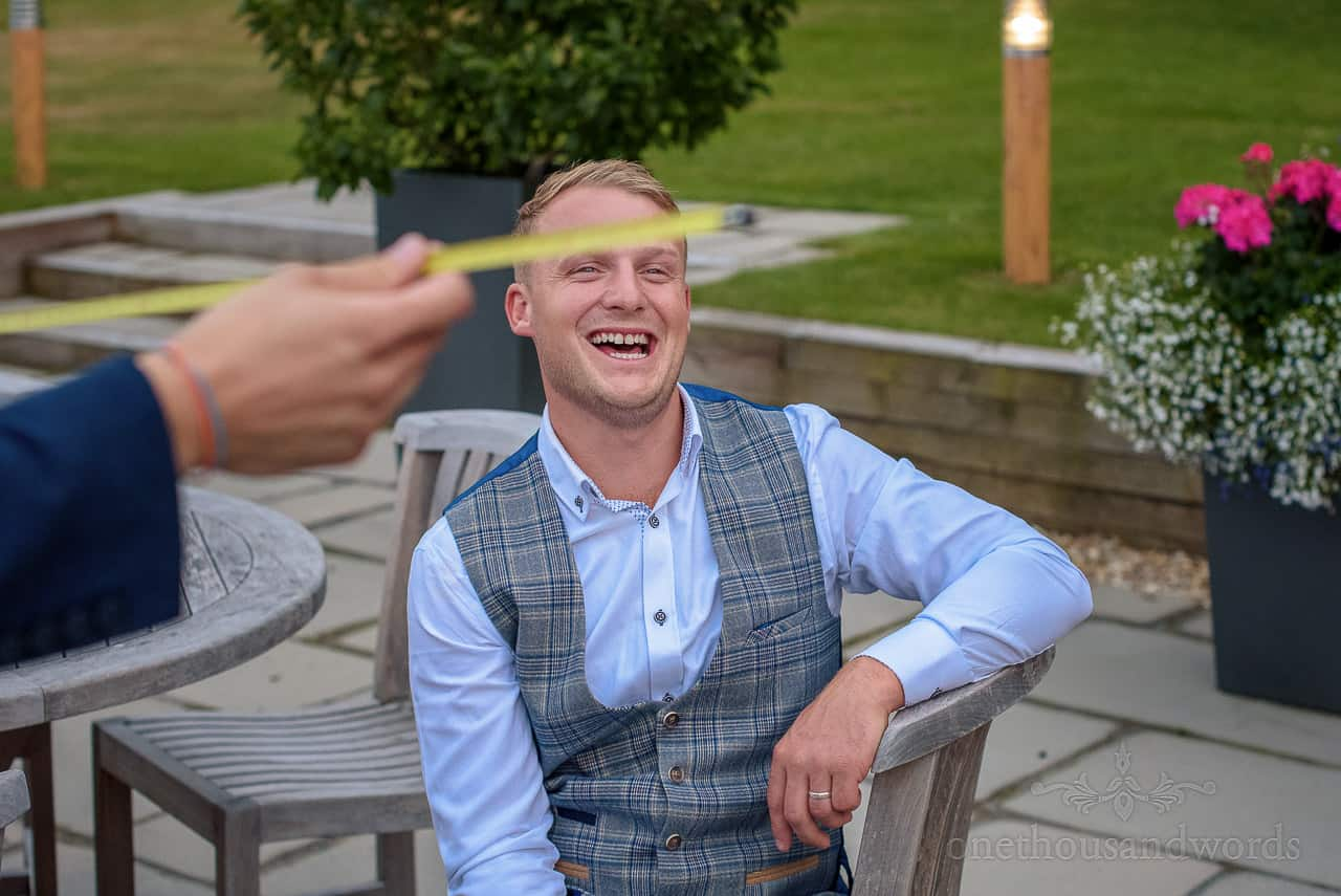 Best man laughing at wedding magician's tape measure trick