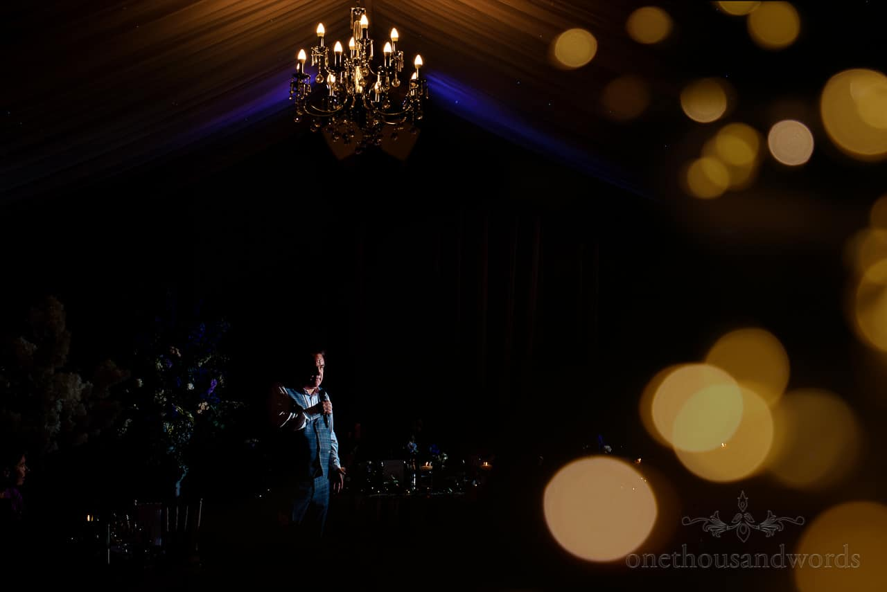 Best man makes wedding speech surrounded by flowers under glowing chandelier at marquee wedding reception