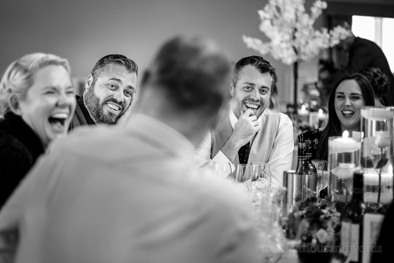 Black and white wedding photo of guests laughing at jokes during wedding breakfast