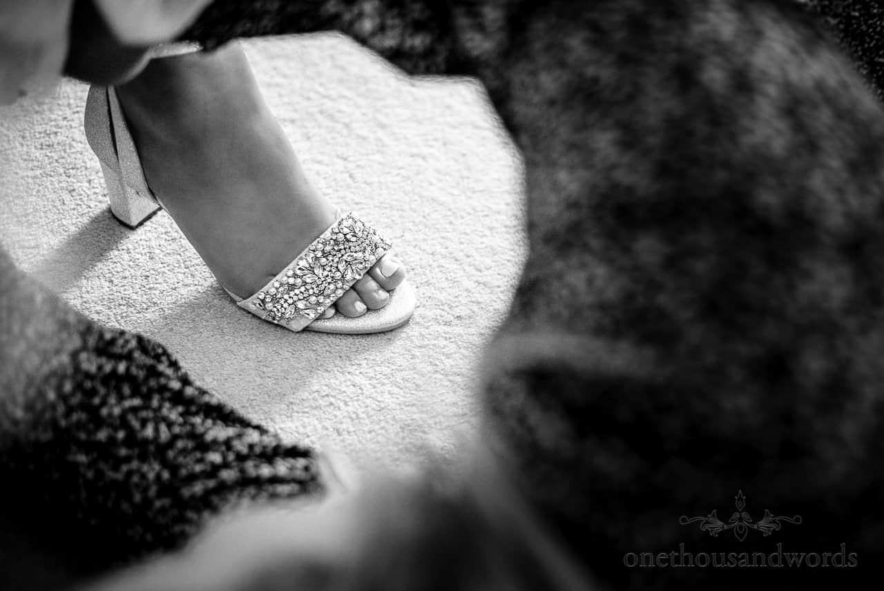 Bridal diamante wedding shoe is fitted, documentary wedding photo