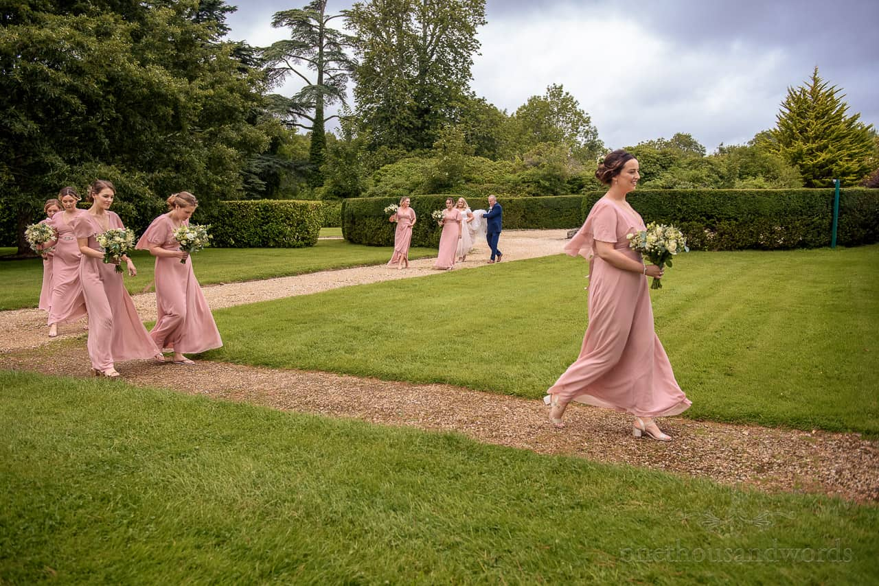Bridal party walk through gardens at Hethfelton House wedding venue