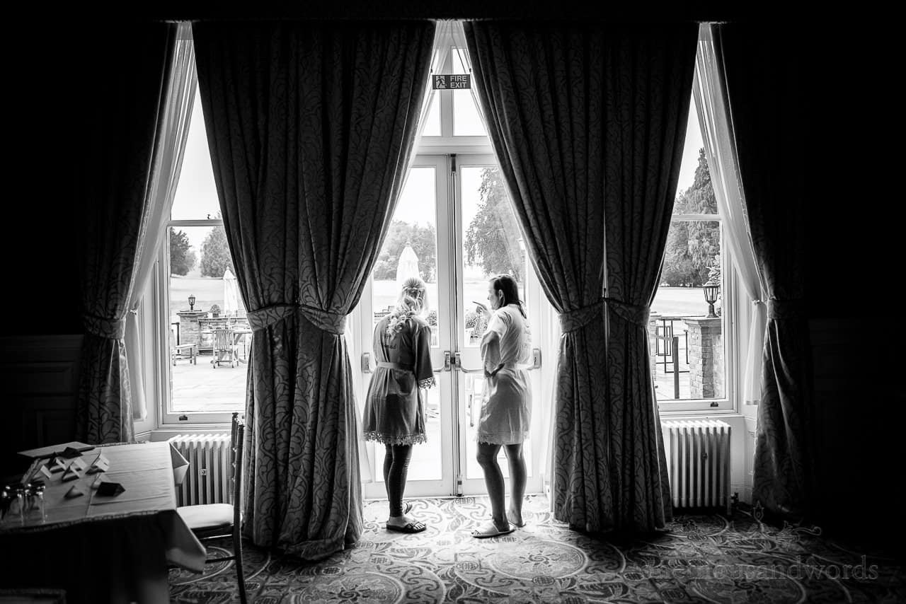 Bride and bridesmaid look out of Oakley Hall wedding ceremony room in the morning